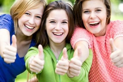 great group of girls with their thumbs up smiling photo